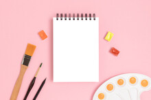 Empty Notepad Mockup And Tools For Painting On A Pink Background. Artistic Workspace With Copyspace.
