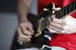 Dłoń gitarzysty na gryfie gitary elektrycznej