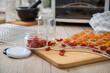 Getrocknete Cherrytomaten gelb und rot auf Dörrautomat Edelstahl Gitter und in Schraubglas für Vorratskammer Lager in Küche auf Holz Hintergrund hell