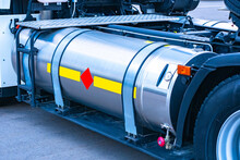 LPG Tank On A Truck. A Silver LPG Tank Next To Wheels Of A Large Truck. It Is Designed For Refueling A Truck With Gas. Refueling Lorry With Methane And Propane. Sale Of LPG Equipment.