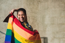 Smiling Ethnic Woman With Rainbow Flag On Beige Background