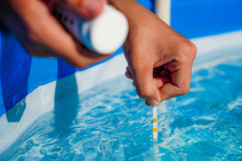 Checking The Water Quality Of A Pool With The Help Of A Test Strip With PH Value, Chlorine And Algaecide