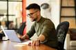Leinwandbild Motiv Young businessman using laptop in his office. Handsome man working on laptop