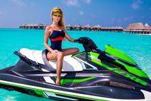 Sexy Tanned Woman Bikini Model At Maldives Tropical Sand Beach. Glamour Girl In Swimsuit On The Jet Ski. Perfect Body Bikini Model Long Blonde Hair. Girl On The Jet Ski. Water Sports, Lifestyle.