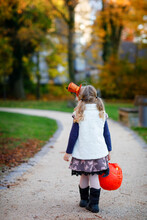 Little Toddler Girl Dressed As A Witch Trick Or Treating On Halloween. Happy Child Outdoors, With Orange Funny Hat And Pumpkin Bag For Sweet Haunt. Family Season In October. Unrecognizable Face