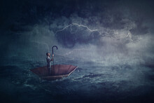 Person Sailing Alone The Ocean On An Umbrella Boat, Looking For Shore. Surreal Scene With A Storm Over The Sea. Fantastic Adventure Concept. Business Despair Metaphor, Conquering And Facing Adversity