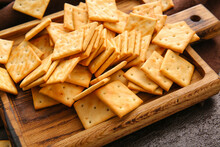 Board With Tasty Crackers On Table, Closeup