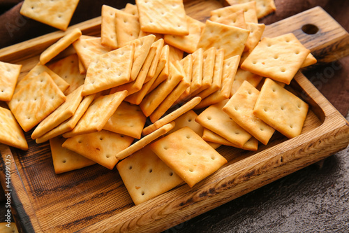 Board with tasty crackers on table, closeup Fototapet