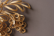 The Branch With Leaves Is Made Of Straw. Straw Wall Decoration. The Products Are Made Of Straw. Decoration Of Straw On A Gray Background.