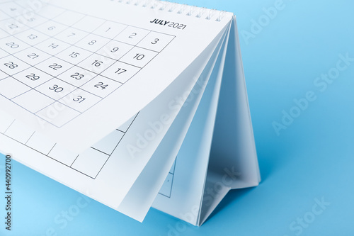 Photo Flip calendar with page of July on color background, closeup