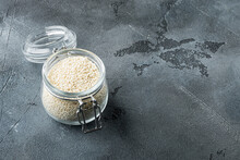 White Sesame Seeds, In Glass Jar, On Gray Stone Background , With Copyspace  And Space For Text