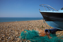 Turquoise And Orange Fishing Net On A Shingle Beach Next To A Fishing Boat With Clear Blue Sea And Sky In The Background.