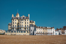Victorian Hotel Buildings On The Seafront In Eastbourne Under A Clear Blue Sky With An Empty Beach In The Foreground.