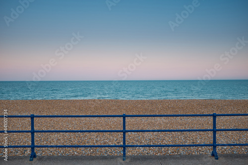 Canvastavla Blue painted metal railings in front of open, empty, shingle beach on Eastbourne promenade