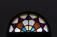 Semi-circular Multicolored Stained Glass Window And Dark Wall