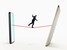 A Man Walks A Tightrope From Smartphone To Digital Tablet. Risk, Balance Concept.