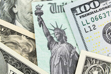 Macro View Of The Statue Of Liberty On A United States Treasury Check With Currency In Background.