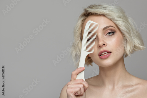 Foto Portrait of a beautiful blonde girl holding a comb in her hand