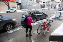 Female Bike Messenger With Bag And Bicycle In Winter City