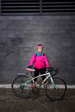 Portrait Confident Female Bike Courier With Bicycle At Alley Wall