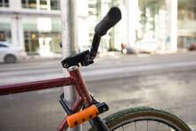 Close Up Bicycle Locked To Post Along Urban Street