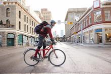 Male Bike Messenger Riding Bicycle Across Wet Winter City Street