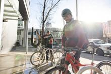 Male Bike Messengers Unlocking Bicycles At Bike Rack In Sunny City