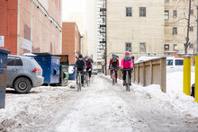 Bike Messengers Riding Bicycles In Snowy City Alley
