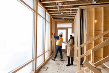 Homebuilder And Architect Inspecting Framing At Construction Site