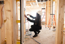 Female Homebuilder Inspecting Wiring At Home Construction Site