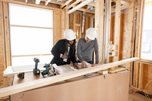 Homebuilders Reviewing Blueprints At Home Construction Site