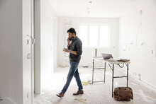 Male Architect Talking On Smart Phone At Home Construction Site