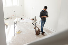 Male Architect With Smart Phone At Home Construction Site