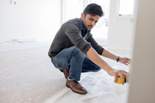 Male Homebuilder With Tape Measure At Home Construction Site