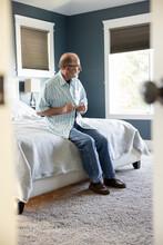 Senior Man Buttoning Shirt On Bed