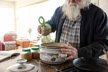 Man Seasoning Stew In Kitchen