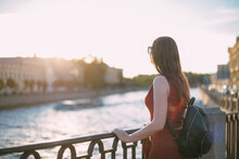 Portrait Of A Beautiful Young Woman On The Embankment Of The River At Sunset In Summer.