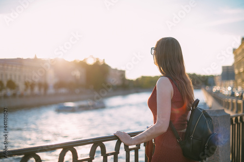 Fotografija Portrait of a beautiful young woman on the embankment of the river at sunset in summer