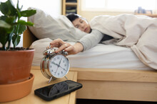 Woman In Bed Snoozing Morning Alarm Clock