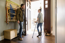 Wife With Forearm Crutches Talking To Husband In Home Foyer