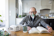 Senior Man With Oxygen Mask Reading Book At Kitchen Table