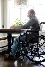Senior Man In Wheelchair With Oxygen Mask At Dining Table