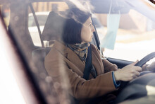 Woman Driving Car With Face Mask Hanging On Rear View Mirror