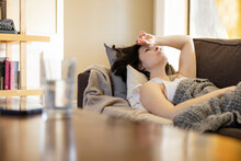 Frustrated Sick Woman Resting On Living Room Sofa With Blanket