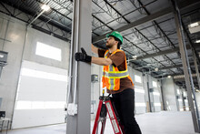 Contractor Working On Ladder In New Building