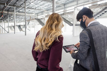 Man Using Augmented Reality On Tablet In Empty Warehouse