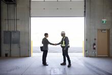 Two Men Shaking Hands In Loading Door Of Empty Warehouse