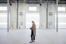 Professional Woman Using Phone In Empty Warehouse