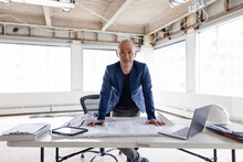 Portrait Of Architect Looking At Plans In Office