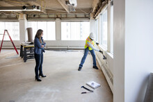 Construction Worker Knocking Hole In Empty Office Wall